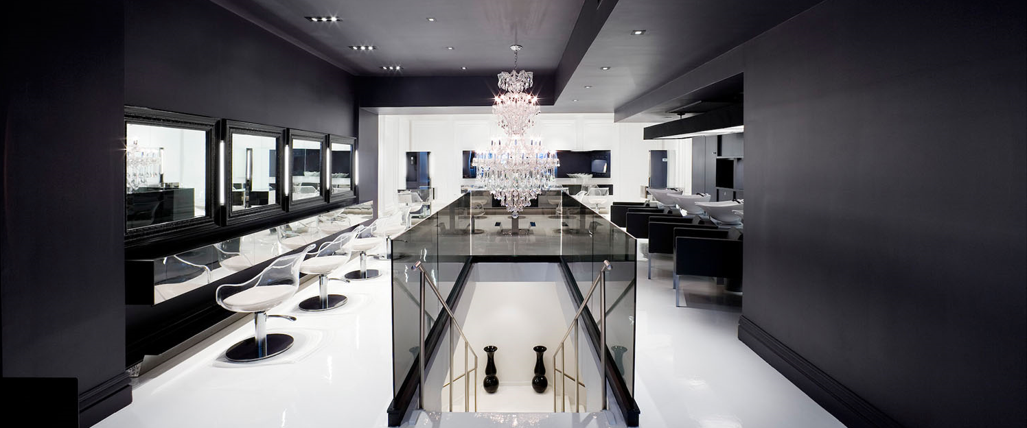 luxury black and white hair salon with modern decor, a chandelier and stairs which go down