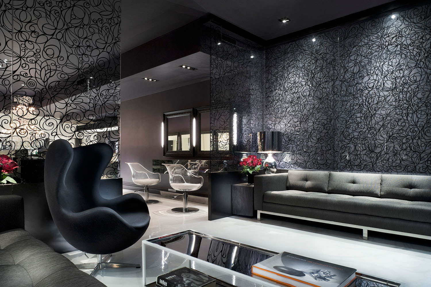 luxury hair salon waiting area with black couches, glass tables and crafted pane windows