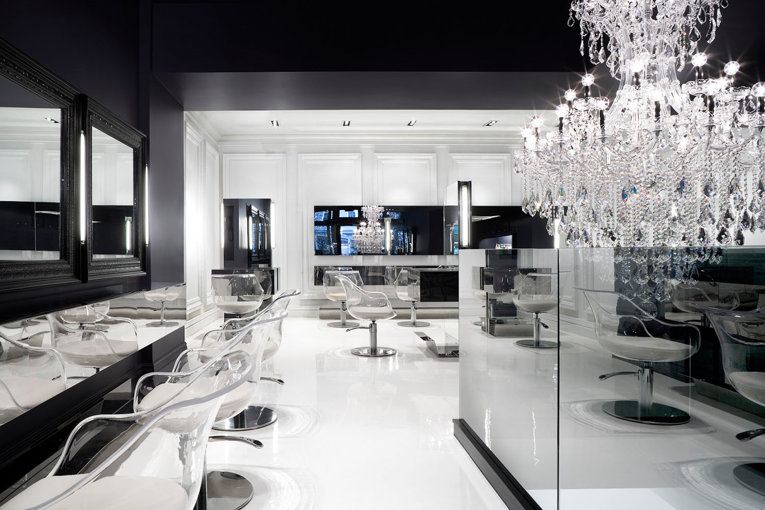 black and white hair salon with modern rotating chairs and crystal chandelier