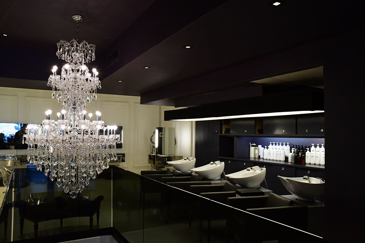 black hair salon with white sinks and a large chandelier