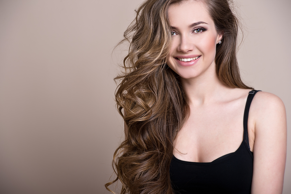 smiling woman with brown wavy hair wearing a  black top