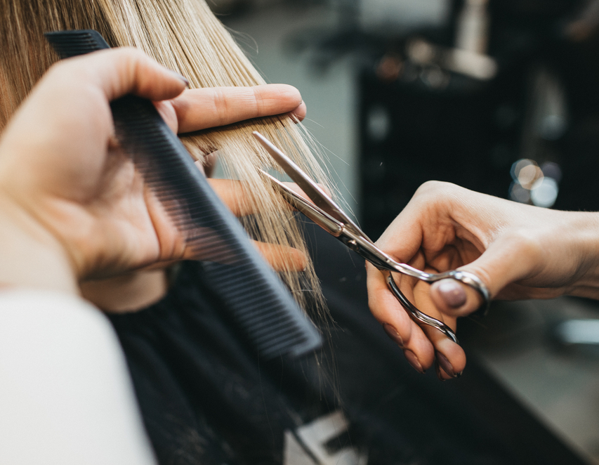 hair stylist holding scissors and a comb cutting blonde hair