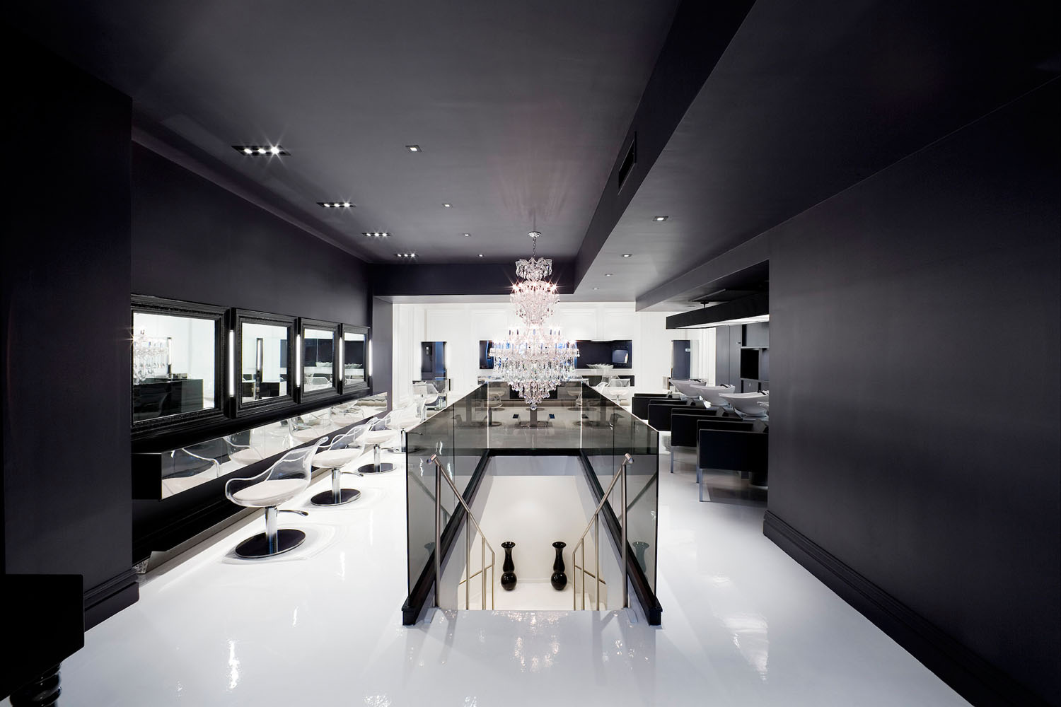 Black and white salon interior with chandelier, stairs and mirrors